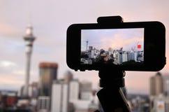 拍摄和摄制在雨云的手机一条彩虹 免版税库存图片
