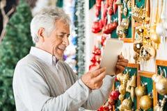 拍摄圣诞节装饰品的愉快的人在 免版税库存照片
