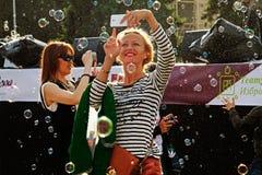 拍摄在一个手机的微笑的妇女肥皂泡在节日`启发`在莫斯科 免版税图库摄影