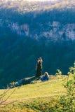 拍摄在一件黑礼服的女孩摄影师一个模型户外在岩石和森林在一个春日 免版税图库摄影