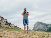 拍摄在一台专业照相机的摄影师男性游人自然 免版税图库摄影
