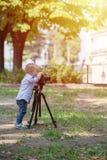 拍摄在三脚架的照相机的小男孩在公园 免版税库存图片