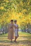 拍摄在夏天黄色花bloo的两个亚洲人妇女一张照片 库存照片