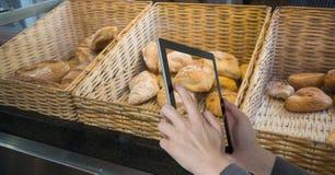 拍摄在片剂个人计算机的手面包在咖啡店 库存图片
