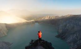 拍摄在观光的点的旅客照片在kawah Ijen火山的湖在早上、著名旅游胜地和旅行d 库存照片
