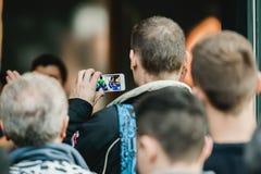 拍摄在他的smarthone苹果计算机商店入口的人 免版税库存图片