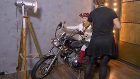 拍摄女孩模型的妇女摄影师摆在摩托车在照相馆 股票视频