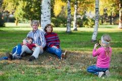 拍摄她的家庭的年轻俏丽的女孩由电话在秋天公园 库存图片