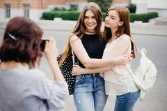 拍摄她的朋友的妇女在城市背景 库存照片