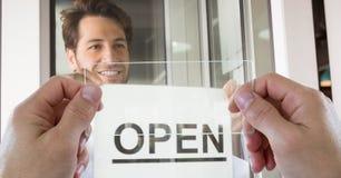 拍摄开放标志的手通过透明设备,当微笑在咖啡店时的人 库存照片