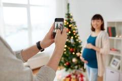 拍摄怀孕的鼓笛的丈夫在圣诞节 库存图片