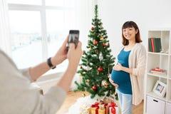 拍摄怀孕的鼓笛的丈夫在圣诞节 免版税库存照片