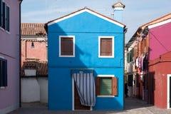 拍摄承担一个晴天在Burano,威尼斯海岛上的明亮地色的房子正方形的蓝色房子  免版税库存照片