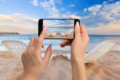 拍摄旅行概念-妇女在海和五颜六色的天空附近拍两张海滩睡椅的照片在沙子的 库存图片