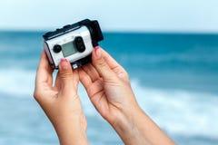 拍摄有索尼行动凸轮的X3000的女性手录影在海 免版税库存图片