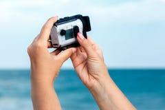 拍摄有索尼行动凸轮的X3000的女性手录影在海 免版税库存照片