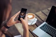拍摄杯子的咖啡有巧妙的电话的妇女 免版税图库摄影