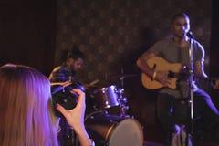 拍摄歌手和音乐家的妇女在夜总会 免版税库存图片