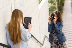 拍摄照片的两名年轻旅游妇女户外 免版税库存图片