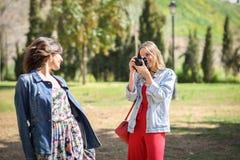 拍摄照片的两名年轻旅游妇女户外 免版税图库摄影