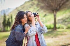 拍摄照片的两名年轻旅游妇女户外 库存图片