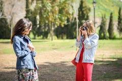 拍摄照片的两名年轻旅游妇女户外 免版税库存照片