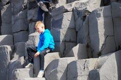 拍摄照片的未认出的男孩在Reynisdrangar海滩在冰岛 免版税图库摄影