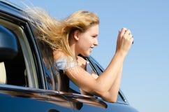 拍摄照片的汽车的妇女 免版税图库摄影