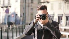 拍摄照片的英俊的年轻男性摄影师室外 股票录像
