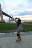 拍摄瓦斯科・达伽马桥梁的照片溜冰者女孩 库存图片