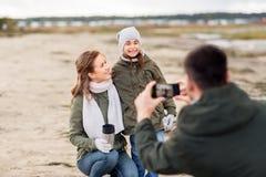 拍摄由在秋天海滩的智能手机的家庭 库存照片