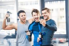 拍摄由智能手机的三个朋友在体育俱乐部 库存图片