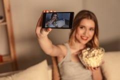 拍摄的逗人喜爱的白肤金发的妇女在电话 免版税库存照片