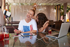 拍摄的年轻愉快的妇女在手机通过自已棍子,当坐在现代咖啡店时 免版税库存图片