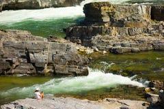 拍摄美妙的瀑布的妇女在冰川国家公园附近夏令时 库存照片