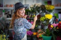 拍摄花的照片从数字式片剂的女性卖花人在花店 免版税库存照片