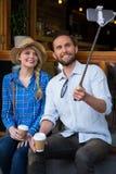 拍摄通过selfie的微笑的夫妇在咖啡店黏附 免版税库存图片