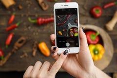 拍摄食物的妇女由电话 库存照片