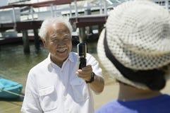 拍摄妻子的老人使用照相机打电话户外 图库摄影