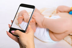 拍摄婴孩概念-六个月婴孩佩带的尿布的脚 免版税库存照片