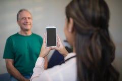 拍摄从手机的女性治疗师背面图资深男性患者 免版税库存图片