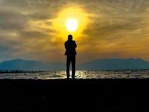 拍日落的照片的摄影师 库存图片