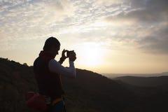 拍日落的照片的登山家 库存照片