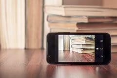 拍旧书的照片与智能手机的 图库摄影