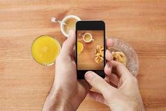拍早餐的照片与智能手机的手 免版税库存照片