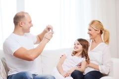 拍母亲和女儿的照片愉快的父亲 免版税库存照片
