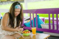 拍水果沙拉的照片与手机网络的年轻愉快和相当数字式游牧人亚裔中国女孩在互联网soc上 库存照片