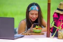 拍水果沙拉的照片与手机网络的年轻愉快和相当数字式游牧人亚裔中国女孩在互联网soc上 免版税图库摄影