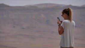 拍沙漠火山口的全景照片的在她的电话的少妇 库存照片