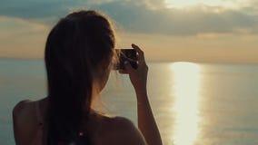 拍河的照片后面观点的一个美丽的女孩在日落 拍在智能手机的照片 股票录像